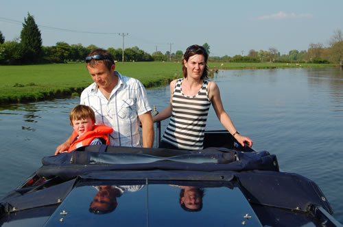 man, woman and child standing on back of narrowboat on the river
